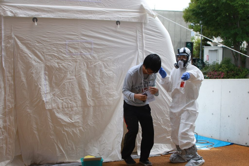 感染症対策用防護服を装着し除染にあたる職員(NBC災害患者除染エリア)の写真