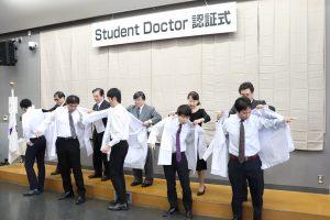 学生に白衣を着せる島田学長ら