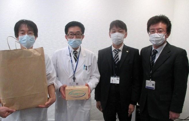 サージカルマスク500枚を寄贈いただきました)よりマスクを受け取る波呂感染制御部長(左)