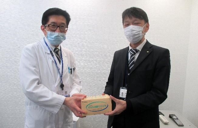 昭和町長代理の内藤寛文 副主幹政策秘書係長(右)よりマスクを受け取る波呂感染制御部長(左)