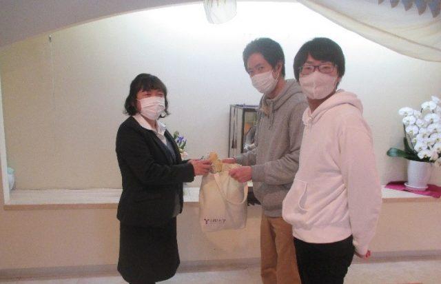 玉穂ケアセンターにマスクを渡す籏原さん(中央)、郡家さん(右)