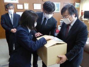 島田学長(右)に手作りマスクを渡す滝本さん(左)
