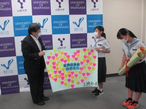 メッセージを紹介する村松さん(右二番目)
