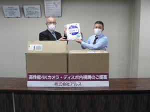 田中吉久代表取締役(右)からガウンを受け取る土屋医学域総務課長(左)