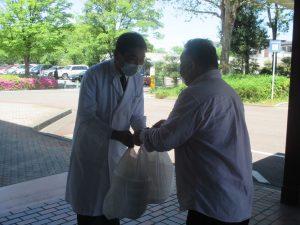 三澤様(右)からカレーライスを受け取る平田修司 教授(左)