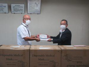 東京電力労働組合山梨地区本部 中田一秀執行委員長(右)からマスクを受け取る土屋医学域総務課長(左)