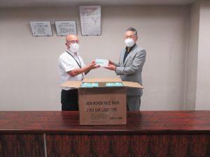 堀内代表取締役(右)からマスクを受取る土屋医学域総務課長(左)