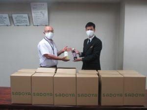 古名屋ホテル営業部萩原課長(右)からワインと ジュースを受取る土屋医学域総務課長(左)