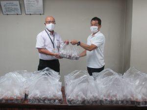 ル・ヴァン長澤斉副施設長(右)からマフィンを受取る土屋医学域総務課長(左)