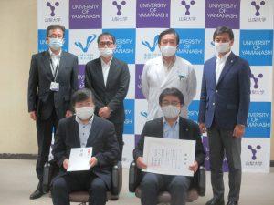 関係者らによる記念写真(前列右)藤原代表取締役社長 (前列左)島田学長