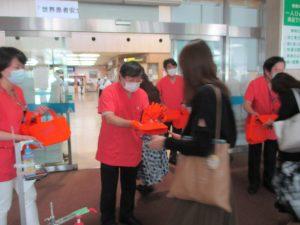 冊子とエコバッグを配付する島田眞路学長(中央)