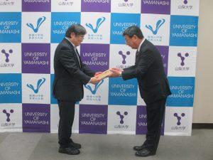 佐藤町長(右)から記念盾を受取る島田学長(左)