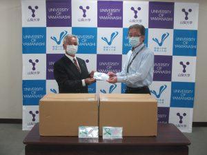 山梨県臓器移植推進財団 高添正彦事務局長(左)からマスクを受け取る野中医学域事務部長(右)