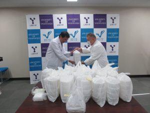 同店経営者の三澤正人氏(右)からカレーライスを受け取る平田修司副病院長(左)