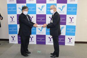 島田学長(左)へ寄附目録を贈呈する田中市長(右)