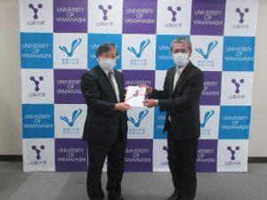 武井代表取締役社長(右)から目録を受領する島田学長(左)